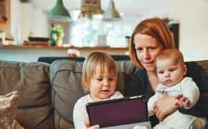 אמא ושני ילדים מביטים בלפטופ