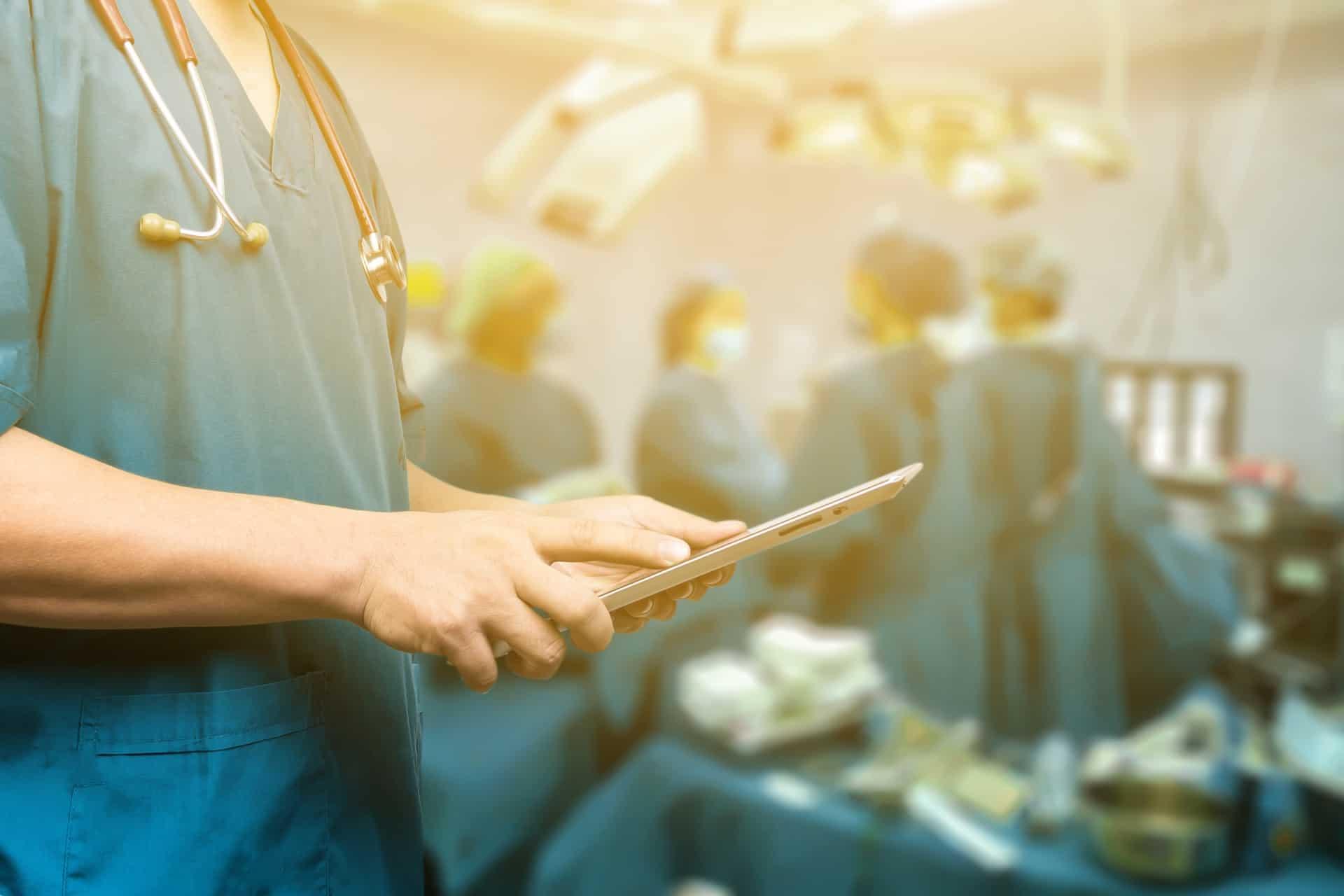 רופא בחדר ניתוח מחזיק אייפד