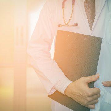 רופא מחזיק לוח ומניח ידו בכיס