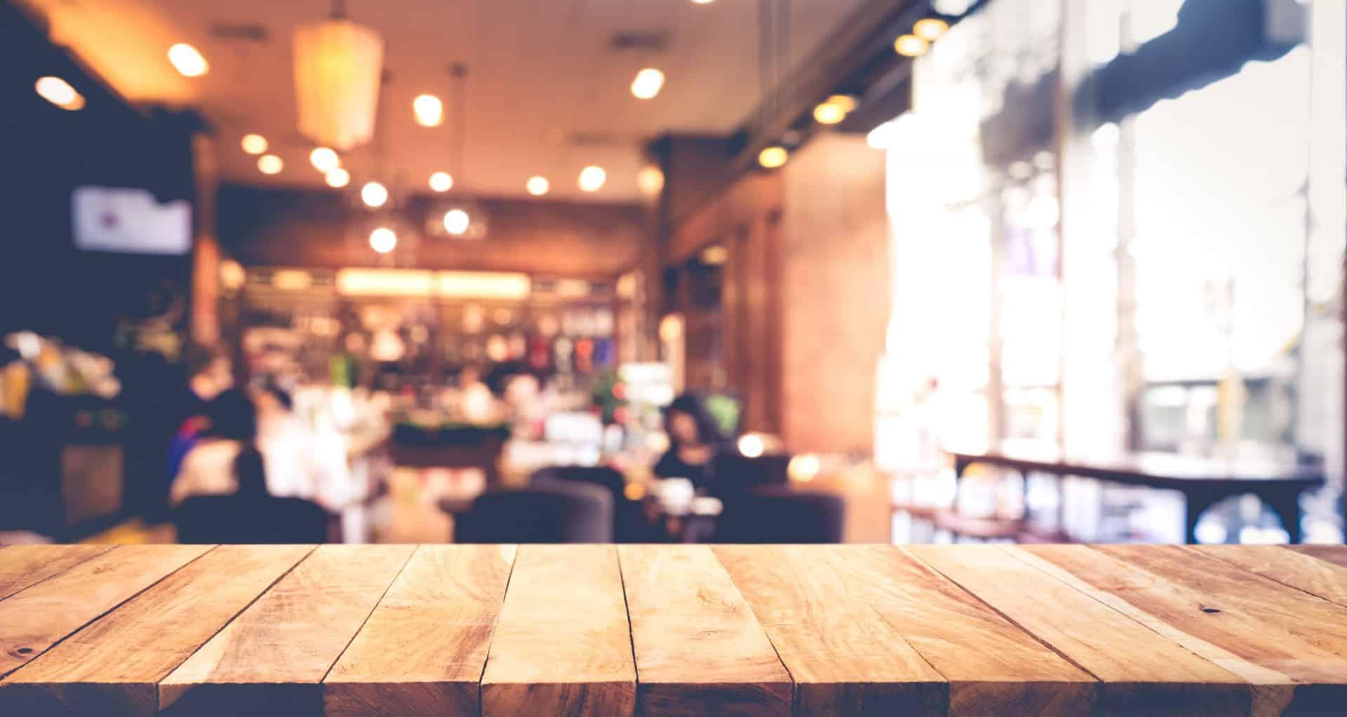 צילום אוירה מטושטש בבית קפה עם שולן מעץ