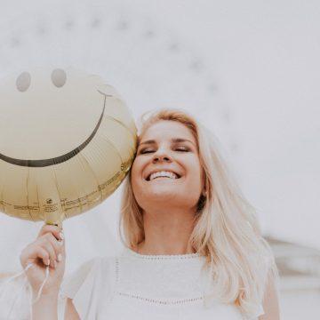 אישה מחייכת מחזיקה בלון עם סמיילי